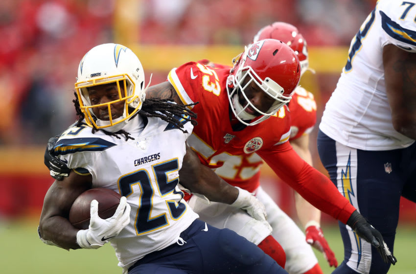 KANSAS CITY, MISSOURI - DECEMBER 29: Running back Melvin Gordon #25 of the Los Angeles Chargers carries the ball as inside linebacker Anthony Hitchens #53 of the Kansas City Chiefs defends at Arrowhead Stadium on December 29, 2019 in Kansas City, Missouri. (Photo by Jamie Squire/Getty Images)