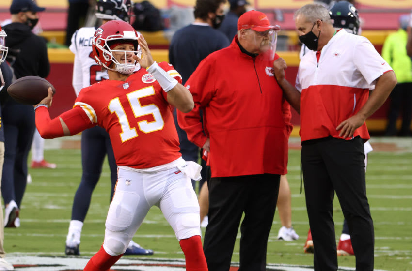 KANSAS CITY, MISSOURI - SEPTEMBER 10: Patrick Mahomes #15 of the Kansas City Chiefs throws as head coach Andy Reid talks in the background wearing a clear face shield before the start of a game against the Houston Texans at Arrowhead Stadium on September 10, 2020 in Kansas City, Missouri. (Photo by Jamie Squire/Getty Images)