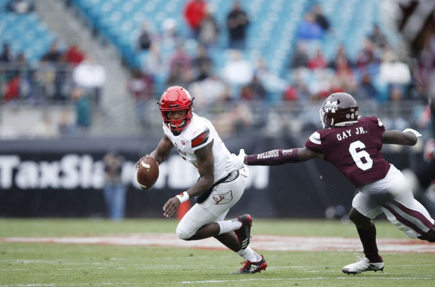 JACKSONVILLE, FL - DECEMBER 30: Lamar Jackson #8 of the Louisville Cardinals looks to pass while under pressure from Willie Gay Jr. #6 of the Mississippi State Bulldogs during the TaxSlayer Bowl at EverBank Field on December 30, 2017 in Jacksonville, Florida. The Bulldogs won 31-27. (Photo by Joe Robbins/Getty Images)