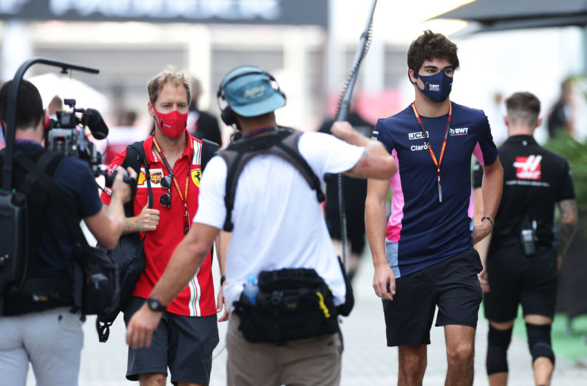SOCHI, RUSSIA - SEPTEMBER 25: Sebastian Vettel of Germany and Ferrari and Lance Stroll of Canada and Racing Point are surrounded by a TV crew as they walk into the paddock before practice ahead of the F1 Grand Prix of Russia at Sochi Autodrom on September 25, 2020 in Sochi, Russia. (Photo by Peter Fox/Getty Images)