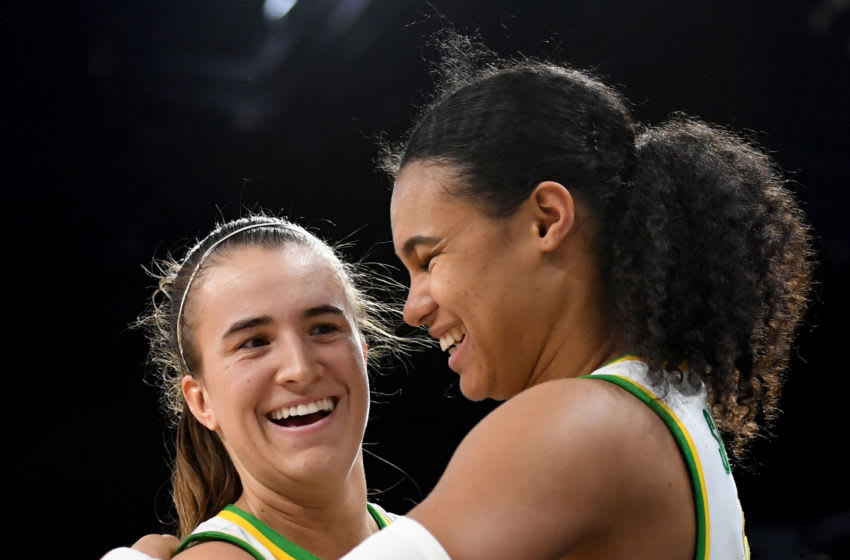 LAS VEGAS, NEVADA - MARCH 08: Sabrina Ionescu #20 and Satou Sabally #0 of the Oregon Ducks hug as they come out of the game late in their 89-56 victory over the Stanford Cardinal during the championship game of the Pac-12 Conference women's basketball tournament at the Mandalay Bay Events Center on March 8, 2020 in Las Vegas, Nevada. (Photo by Ethan Miller/Getty Images)