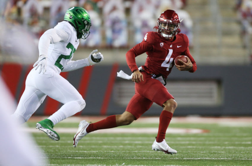 PULLMAN, WASHINGTON - NOVEMBER 14: Jayden de Laura #4 of the Washington State Cougars carries the ball against Adrian Jackson #29 of the Oregon Ducks in the first half at Martin Stadium on November 14, 2020 in Pullman, Washington. (Photo by William Mancebo/Getty Images)