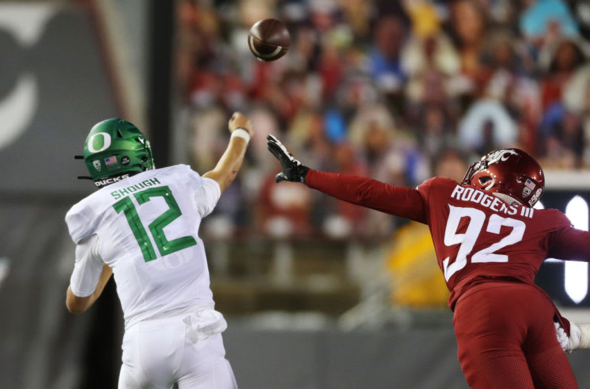 PULLMAN, WASHINGTON - NOVEMBER 14: Quarterback Tyler Shough #12 of the Oregon Ducks throws a pass against Will Rodgers III #92 of the Washington State Cougars in the first half at Martin Stadium on November 14, 2020 in Pullman, Washington. (Photo by William Mancebo/Getty Images)
