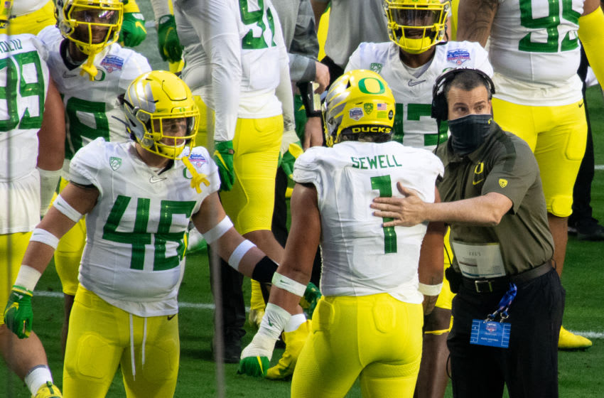 GLENDALE, ARIZONA - JANUARY 02: Head coach Mario Cristobal of the Oregon Ducks congratulates linebacker Noah Sewell #1 on a play during the PlayStation Fiesta Bowl against the Iowa State Cyclones at State Farm Stadium on January 02, 2021 in Glendale, Arizona. (Photo by Jennifer Stewart/Getty Images)