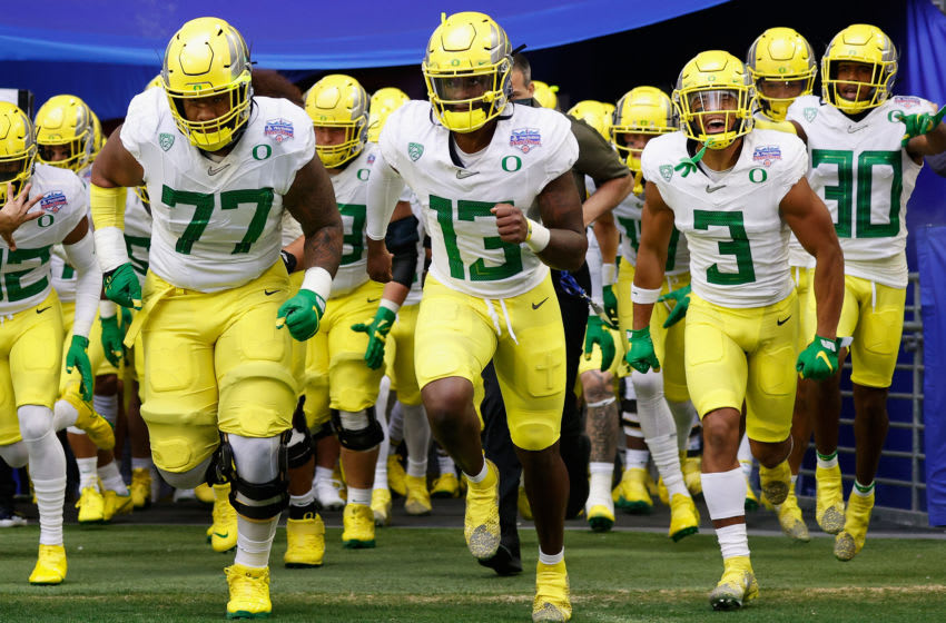 GLENDALE, ARIZONA - JANUARY 02: (L-R) George Moore #77, Anthony Brown #13 and Johnny Johnson III #3 of the Oregon Ducks leads teammates onto the field before the PlayStation Fiesta Bowl against the Iowa State Cyclones at State Farm Stadium on January 02, 2021 in Glendale, Arizona. The Cyclones defeated the Ducks 34-17. (Photo by Christian Petersen/Getty Images)