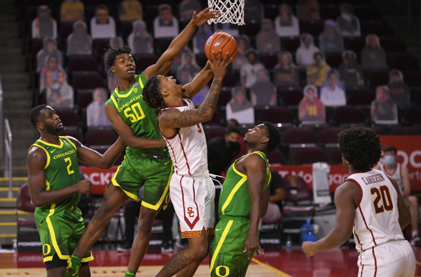 LOS ANGELES, CA - FEBRUARY 22: Isaiah White #5 of the USC Trojans is fouled by Eric Williams Jr. #50 as Amauri Hardy #11 of the Oregon Ducks looks on at Galen Center on February 22, 2021 in Los Angeles, California. USC won 72-58. (Photo by John McCoy/Getty Images)