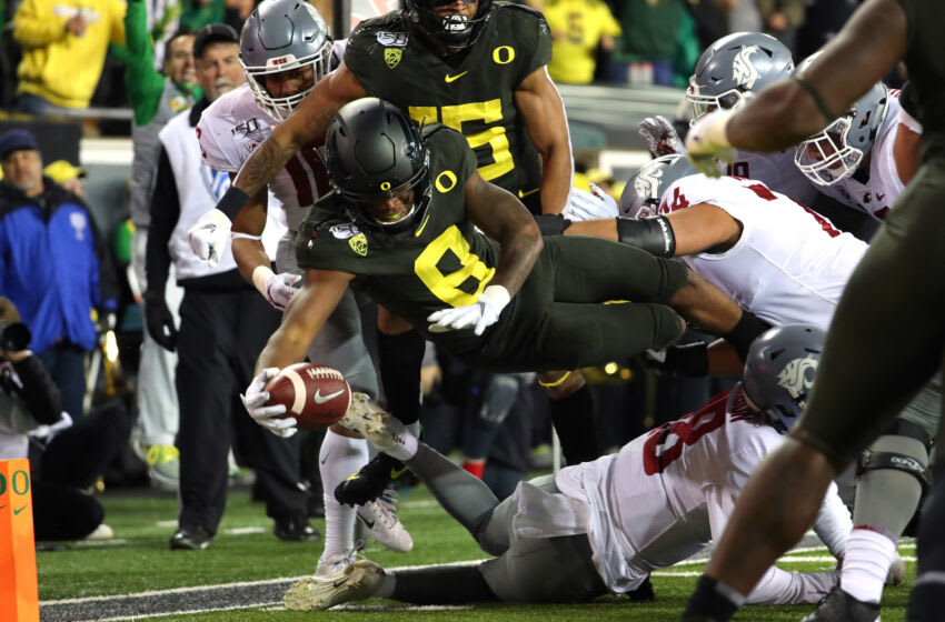 EUGENE, OREGON - OCTOBER 26: Jevon Holland #8 of the Oregon Ducks dives for a 19 yard pick six against the Washington State Cougars in the second quarter during their game at Autzen Stadium on October 26, 2019 in Eugene, Oregon. (Photo by Abbie Parr/Getty Images)