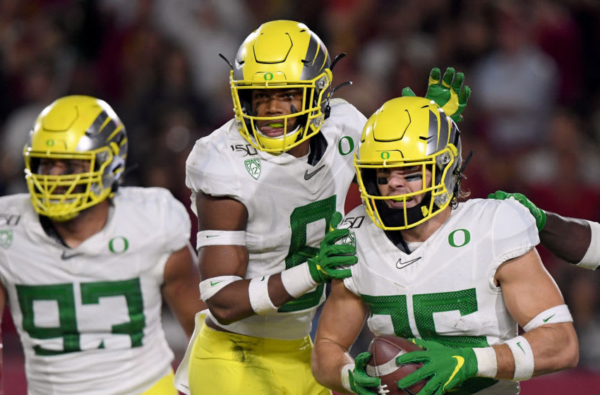 LOS ANGELES, CALIFORNIA - NOVEMBER 02: Brady Breeze #25 of the Oregon Ducks celebrates his touchdown from his interception with Jevon Holland #8 and Sione Kava #93, to take a 21-10 lead over the USC Trojans, during the first half at Los Angeles Memorial Coliseum on November 02, 2019 in Los Angeles, California. (Photo by Harry How/Getty Images)