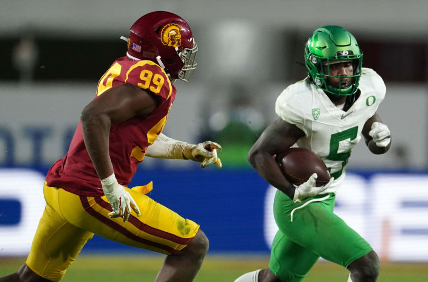 Dec 18, 2020; Los Angeles, California, USA; Oregon Ducks running back Sean Dollars (5) is pursued by Southern California Trojans linebacker Drake Jackson (99) during the Pac-12 Championship at United Airlines Field at Los Angeles Memorial Coliseum. Oregon defeated USC 31-24. Mandatory Credit: Kirby Lee-USA TODAY Sports