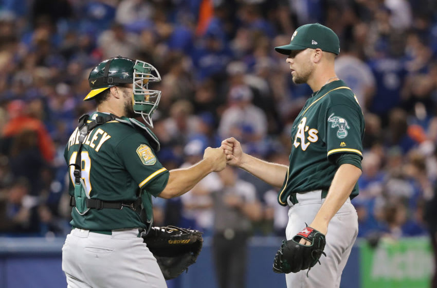 TORONTO, ON - MAY 19: Blake Treinen #39 of the Oakland Athletics celebrates their victory with Josh Phegley #19 during MLB game action against the Toronto Blue Jays at Rogers Centre on May 19, 2018 in Toronto, Canada. (Photo by Tom Szczerbowski/Getty Images)