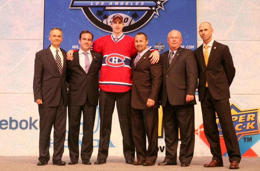LOS ANGELES, CA - JUNE 25: Jarred Tinordi, drafted 22th overall by the Montreal Canadiens, poses on stage with team personnel during the 2010 NHL Entry Draft at Staples Center on June 25, 2010 in Los Angeles, California. (Photo by Bruce Bennett/Getty Images)