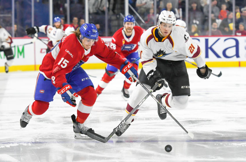 LAVAL, QC, CANADA - JANUARY 19: Phelix Martineau #15 of the Laval Rocket and Sam Vigneault #21 of the Cleveland Monsters chasing the puck at Place Bell on January 19, 2019 in Laval, Quebec. (Photo by Stephane Dube /Getty Images)