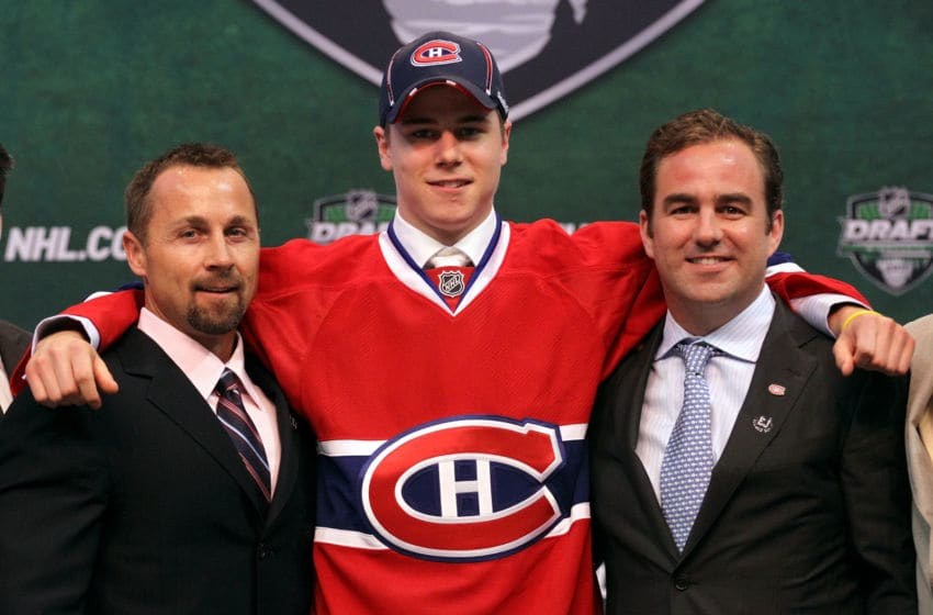 ST PAUL, MN - JUNE 24: Seventh overall pick Nathan Beaulieu by the Montreal Canadiens stands onstage for a photo with Director of Procurement and Player Development Trevor Timmins and a member of the Montreal Canadiens organization during day one of the 2011 NHL Entry Draft at Xcel Energy Center on June 24, 2011 in St Paul, Minnesota. (Photo by Bruce Bennett/Getty Images)