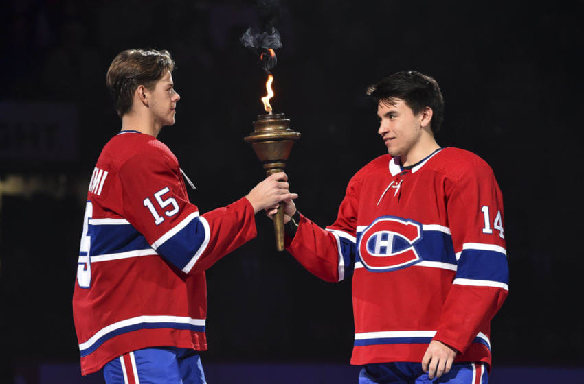 MONTREAL, QC - OCTOBER 10: Jesperi Kotkaniemi #15 of the Montreal Canadiens (L) and teammate Nick Suzuki #14 (R) take part in the opening ceremony prior to their home game against the Detroit Red Wings at the Bell Centre on October 10, 2019 in Montreal, Canada. The Detroit Red Wings defeated the Montreal Canadiens 4-2. (Photo by Minas Panagiotakis/Getty Images)