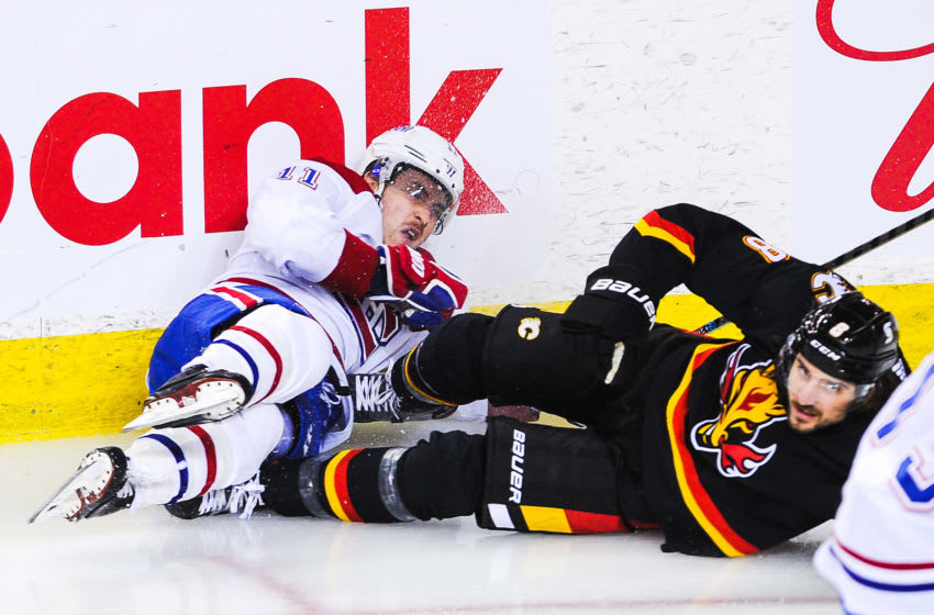 CALGARY, AB - MARCH 11: Christopher Tanev #8 of the Calgary Flames collies with Brendan Gallagher #11 of the Montreal Canadiens during an NHL game at Scotiabank Saddledome on March 11, 2021 in Calgary, Alberta, Canada. (Photo by Derek Leung/Getty Images)