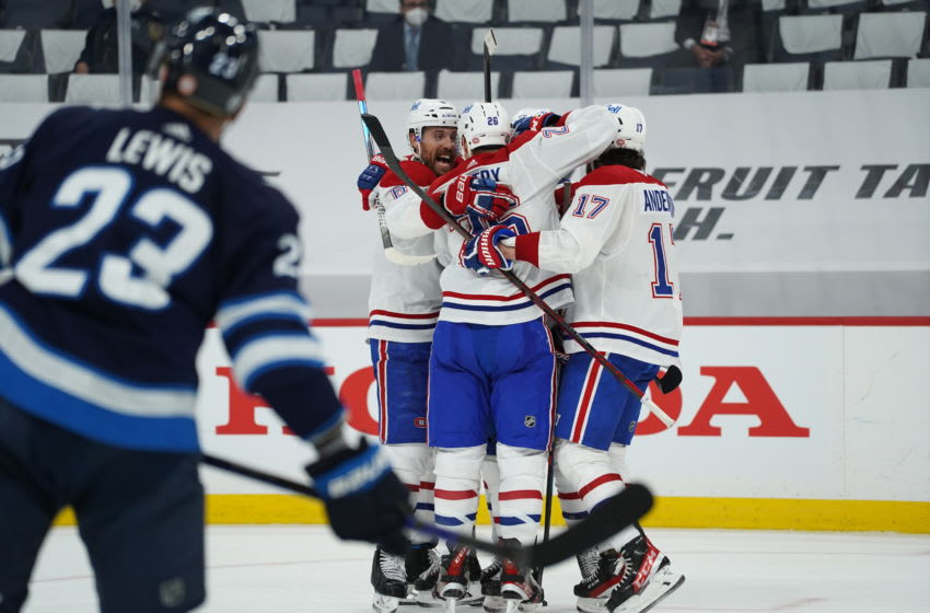 WINNIPEG, MB - JUNE 2: Brendan Gallagher #11 of the Montreal Canadiens celebrates his third period goal with teammates on Connor Hellebuyck #37 of the Winnipeg Jets in Game One of the Second Round of the 2021 Stanley Cup Playoffs on June 2, 2021 at Bell MTS Place in Winnipeg, Manitoba, Canada. (Photo by David Lipnowski/Getty Images)