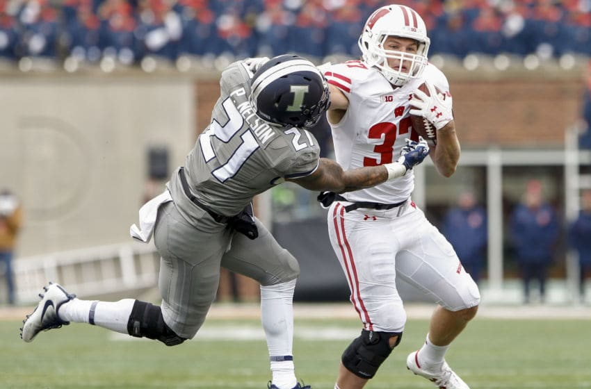 CHAMPAIGN, IL - OCTOBER 28: Garrett Groshek #37 of the Wisconsin Badgers runs the ball and delivers the stiff arm to Patrick Nelson #21 of the Illinois Fighting Illini at Memorial Stadium on October 28, 2017 in Champaign, Illinois. (Photo by Michael Hickey/Getty Images)