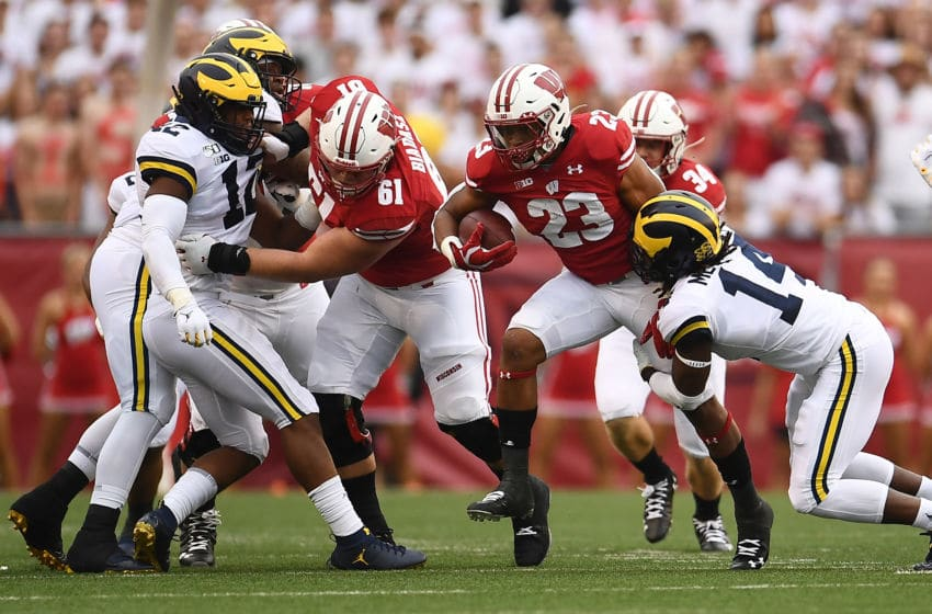 MADISON, WISCONSIN - SEPTEMBER 21: Jonathan Taylor #23 of the Wisconsin Badgers is brought down by Josh Metellus #14 of the Michigan Wolverines during the first half at Camp Randall Stadium on September 21, 2019 in Madison, Wisconsin. (Photo by Stacy Revere/Getty Images)