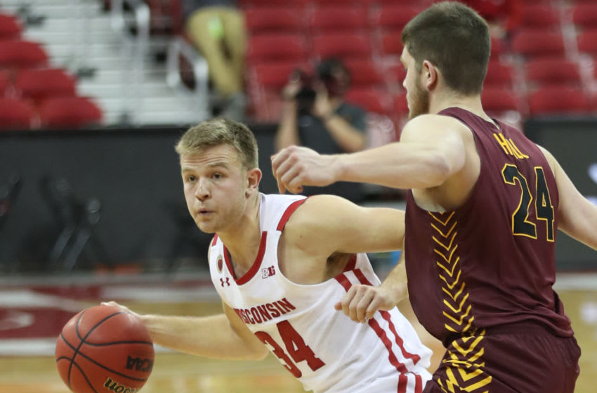 Dec 15, 2020; Madison, Wisconsin, USA; Wisconsin Badgers guard Brad Davison (34) works the ball against Loyola Ramblers guard Tate Hall (24) during the second half at the Kohl Center. Mandatory Credit: Mary Langenfeld-USA TODAY Sports