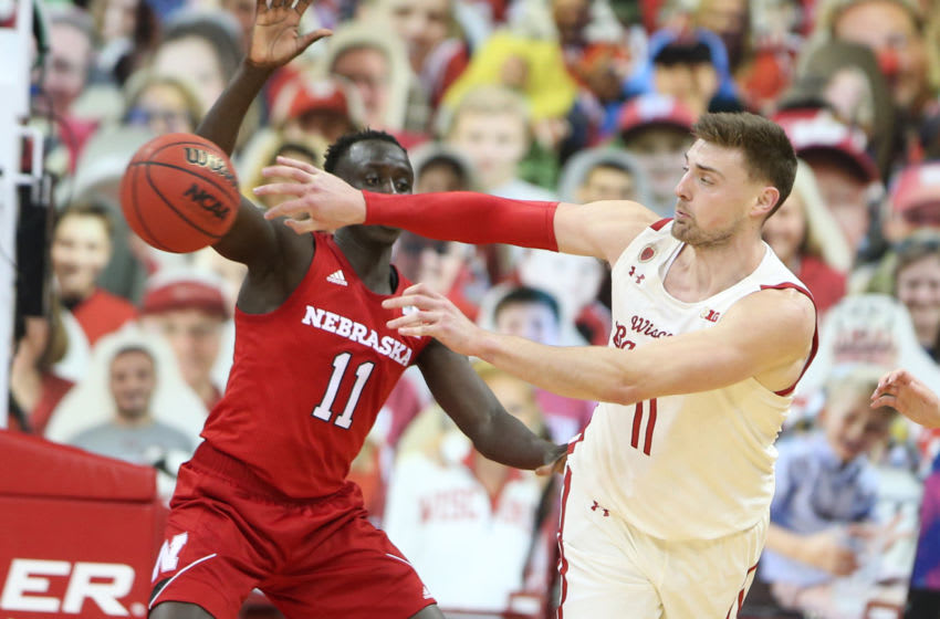 Dec 22, 2020; Madison, Wisconsin, USA; Wisconsin Badgers forward Micah Potter (11) passes the ball past Nebraska Cornhuskers forward Lat Mayen (11) during the second half at the Kohl Center. Mandatory Credit: Mary Langenfeld-USA TODAY Sports