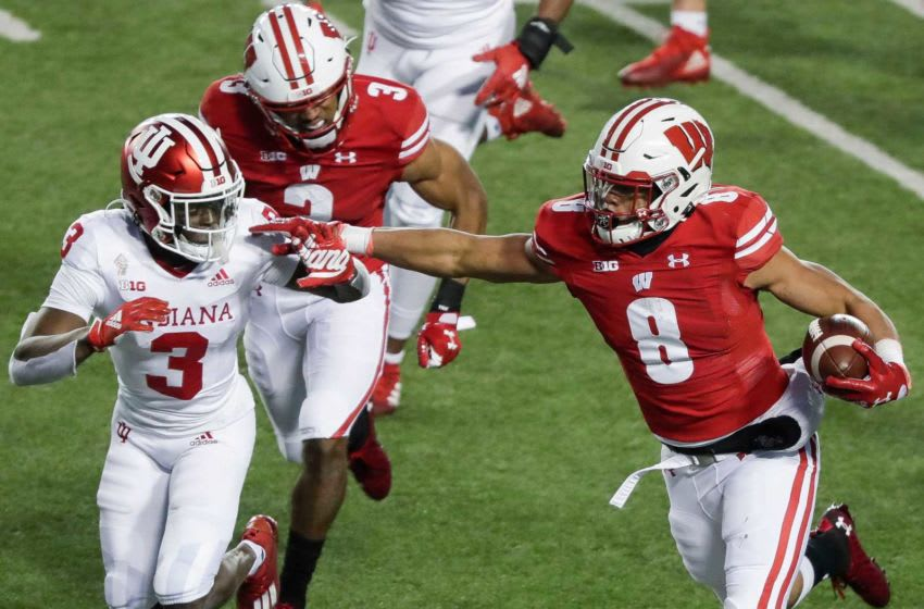 Wisconsin's Jalen Berger (8) stiff-arms Indiana's Tiawan Mullen (3) on Saturday, December 5, 2020, at Camp Randall Stadium in Madison, Wis. Indiana won the game, 14-6. Mjs Usat Wisconsin Vs Indiana Football 120520 2682 Ttm