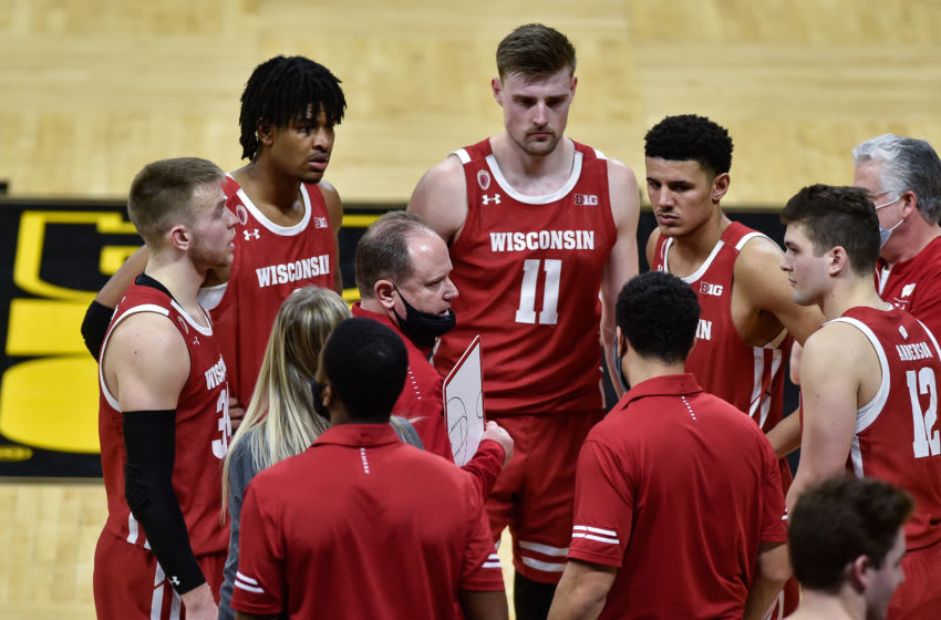 Mar 7, 2021; Iowa City, Iowa, USA; Wisconsin Badgers head coach Greg Gard talks with guard Trevor Anderson (12) and guard Brad Davison (left) and forward Micah Potter (11) late in the game during the second half against the Iowa Hawkeyes at Carver-Hawkeye Arena. Mandatory Credit: Jeffrey Becker-USA TODAY Sports