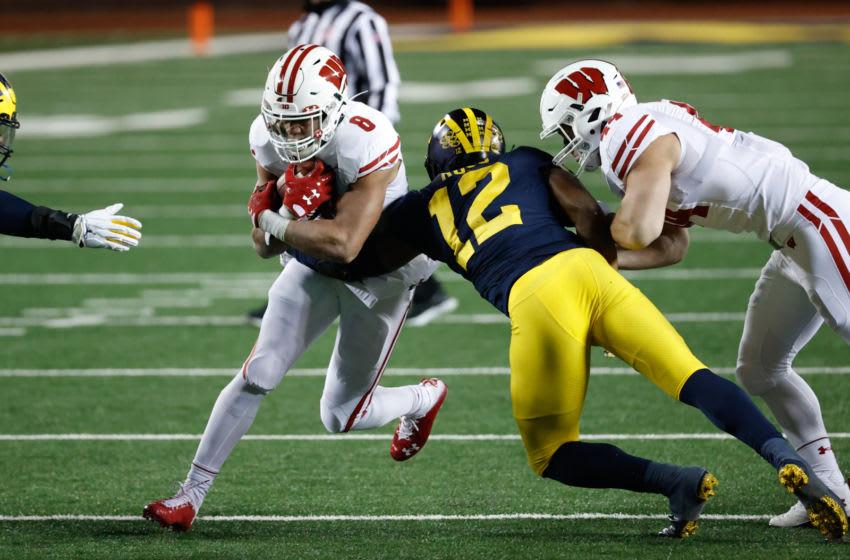 Nov 14, 2020; Ann Arbor, Michigan, USA; Wisconsin Badgers running back Jalen Berger (8) is tackled by Michigan Wolverines linebacker Josh Ross (12) in the second half at Michigan Stadium. Mandatory Credit: Rick Osentoski-USA TODAY Sports