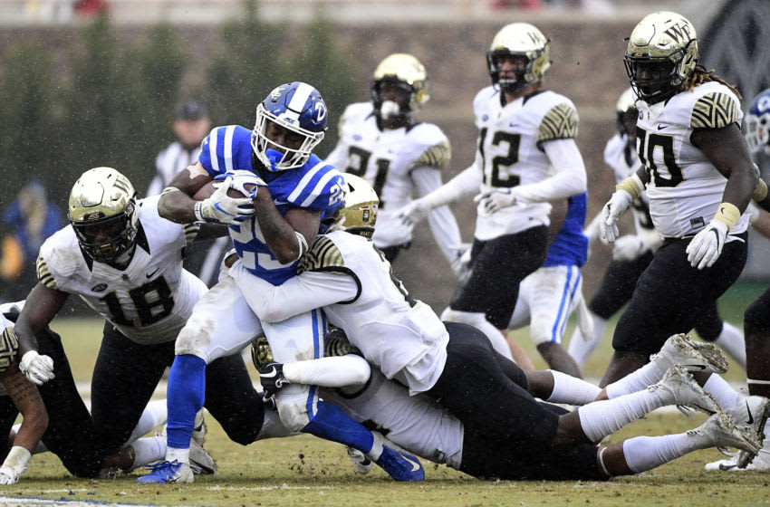 DURHAM, NORTH CAROLINA - NOVEMBER 24: Defensive back Cameron Glenn #2 of the Wake Forest Demon Deacons leads a tackle of running back Deon Jackson #25 of the Duke Blue Devils during their football game at Wallace Wade Stadium on November 24, 2018 in Durham, North Carolina. (Photo by Mike Comer/Getty Images)