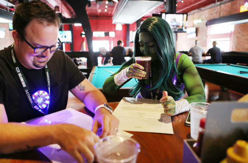 SAN DIEGO, CA - JULY 20: A cosplayer (R) dressed as She-Hulk drinks a beer outside San Diego Comic-Con on July 20, 2018 in San Diego, California. More than 100,000 attendees are expected at the annual comic and entertainment convention. (Photo by Mario Tama/Getty Images)