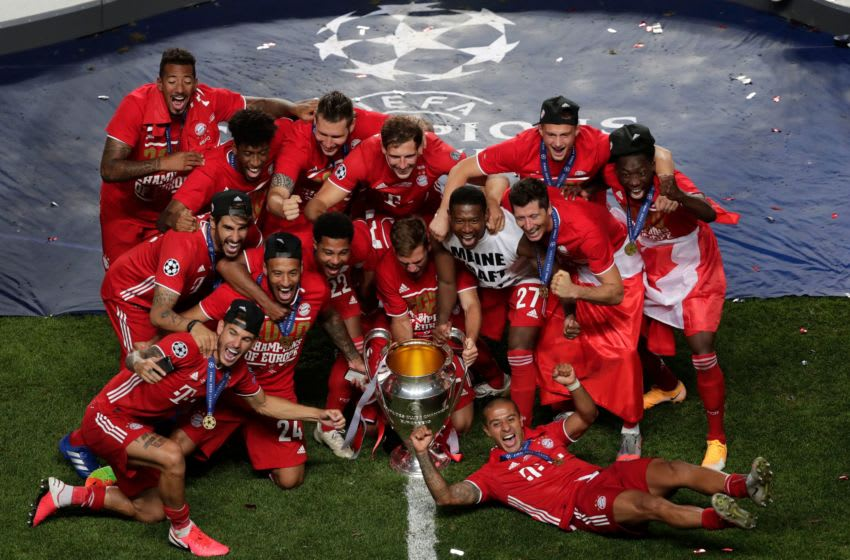 Bayern Munich players celebrate with the Champions League trophy. (Photo by MANU FERNANDEZ/POOL/AFP via Getty Images)