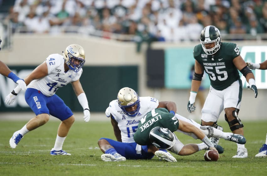 ;Manny BunchEAST LANSING, MI - AUGUST 30: Brian Lewerke #14 of the Michigan State Spartans loses the ball after being sacked by Trevis Gipson #15 of the Tulsa Golden Hurricane in the first quarter at Spartan Stadium on August 30, 2019 in East Lansing, Michigan. (Photo by Joe Robbins/Getty Images)