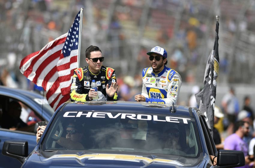 BROOKLYN, MICHIGAN - AUGUST 11: Alex Bowman, driver of the #88 Axalta Chevrolet and Chase Elliott, driver of the #9 NAPA AUTO PARTS Chevrolet, greet the crowd at driver introductions during the Monster Energy NASCAR Cup Series Consumers Energy 400 at Michigan International Speedway on August 11, 2019 in Brooklyn, Michigan. (Photo by Quinn Harris/Getty Images)