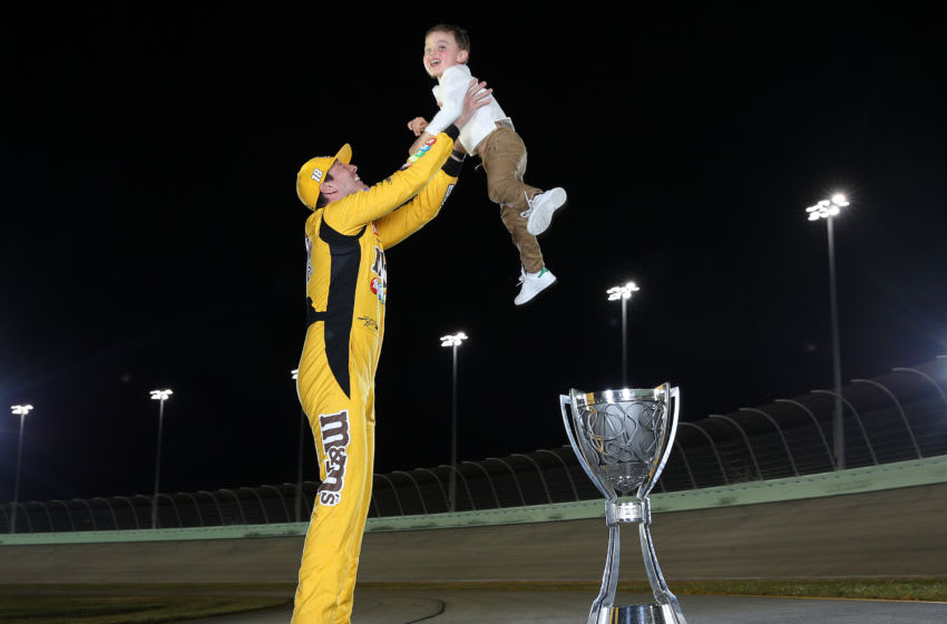 HOMESTEAD, FLORIDA - NOVEMBER 17: Kyle Busch, driver of the #18 M&M's Toyota and his son Brexton pose with the trophy after winning the Monster Energy NASCAR Cup Series Championship at Homestead Speedway on November 17, 2019 in Homestead, Florida. (Photo by Chris Graythen/Getty Images)