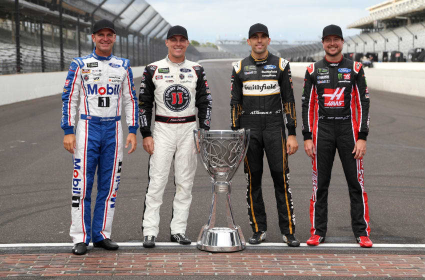 INDIANAPOLIS, IN - SEPTEMBER 10: Clint Bowyer, driver of the #14 Mobil 1/Rush Truck Centers Ford, Kevin Harvick, driver of the #4 Jimmy John's New 9-Grain Wheat Sub Ford, Aric Almirola, driver of the #10 Smithfield Ford, Kurt Busch, driver of the #41 Haas Automation/Monster Energy Ford, pose for a photo with the Monster Energy NASCAR Cup Series trophy after making the playoffs following the Monster Energy NASCAR Cup Series Big Machine Vodka 400 at the Brickyard at Indianapolis Motor Speedway on September 10, 2018 in Indianapolis, Indiana. (Photo by Brian Lawdermilk/Getty Images)