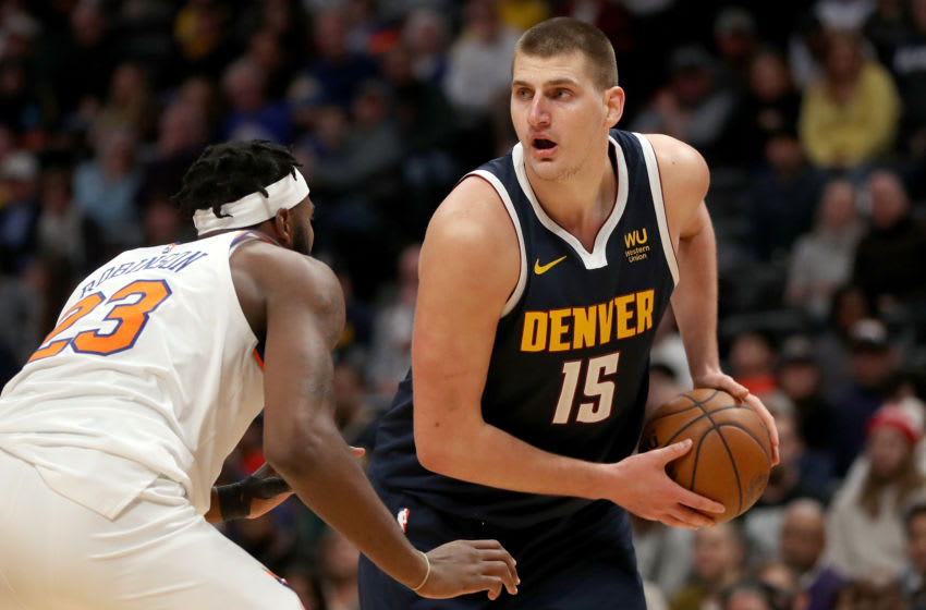 DENVER, COLORADO - DECEMBER 15: Nikola Jokic ##15 of the Denver Nuggets drives against Mitchell Robinson #23 of the New York Knicks in the fourth quarter at the Pepsi Center on December 15, 2019 in Denver, Colorado. NOTE TO USER: User expressly acknowledges and agrees that, by downloading and or using this photograph, User is consenting to the terms and conditions of the Getty Images License Agreement. (Photo by Matthew Stockman/Getty Images)