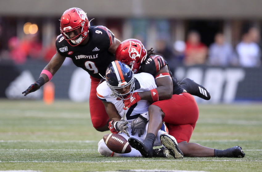 LOUISVILLE, KENTUCKY - OCTOBER 26: C.J. Avery #9 and Boosie Whitlow #49 of the Louisville Cardinals combine to force a fumble by Joe Reed #2 of the Virginia Cavaliers on October 26, 2019 in Louisville, Kentucky. (Photo by Andy Lyons/Getty Images)