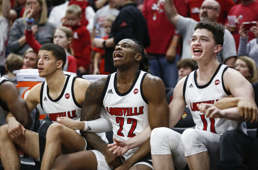 LOUISVILLE, KENTUCKY - FEBRUARY 08: Samuell Williamson #10, Aidan Igehon #22 and Quinn Slazinski #11 of the Louisville Cardinals reacts to their team defeating the Virginia Cavaliers during the final minuets of the game at KFC YUM! Center on February 08, 2020 in Louisville, Kentucky. (Photo by Silas Walker/Getty Images)