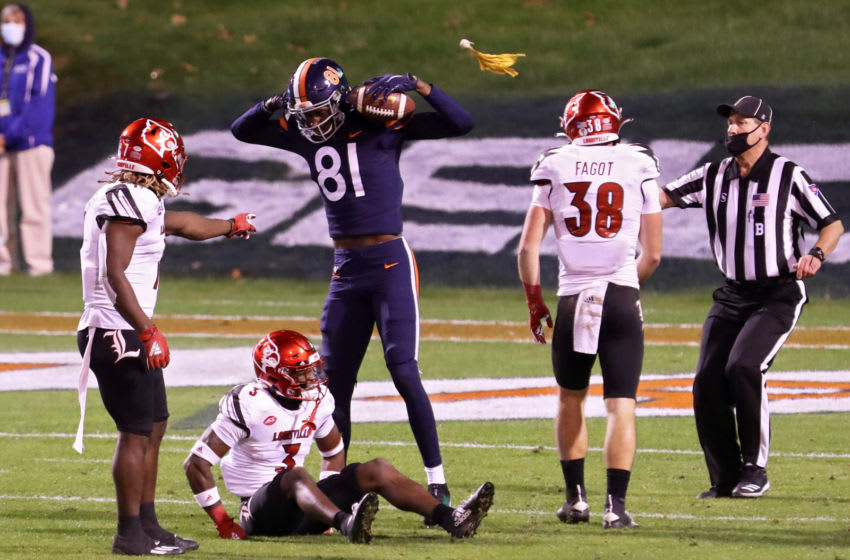 CHARLOTTESVILLE, VA - NOVEMBER 14: Lavel Davis Jr. #81 of the Virginia Cavaliers is penalized for taunting as he flexes over Russ Yeast #3 of the Louisville Cardinals in the second half during a game at Scott Stadium on November 14, 2020 in Charlottesville, Virginia. (Photo by Ryan M. Kelly/Getty Images)