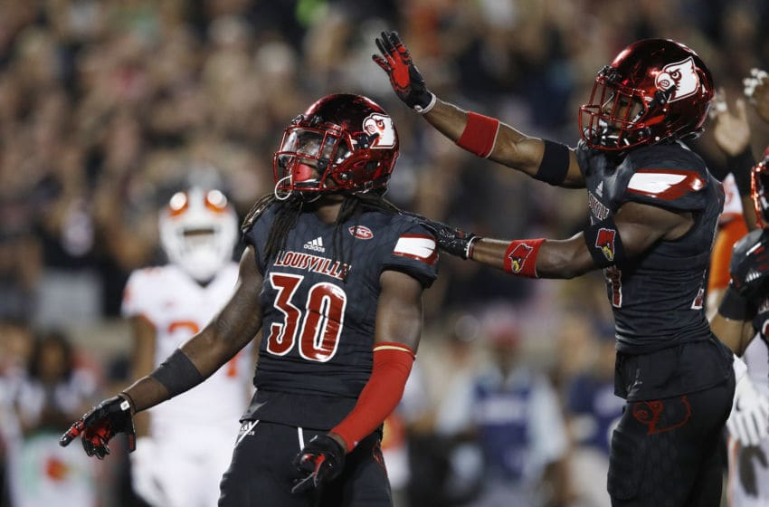 LOUISVILLE, KY - SEPTEMBER 16: Khane Pass #30 of the Louisville Cardinals celebrates with Zykiesis Cannon #24 after a tackle for loss against the Clemson Tigers in the first quarter of a game at Papa John's Cardinal Stadium on September 16, 2017 in Louisville, Kentucky. (Photo by Joe Robbins/Getty Images)