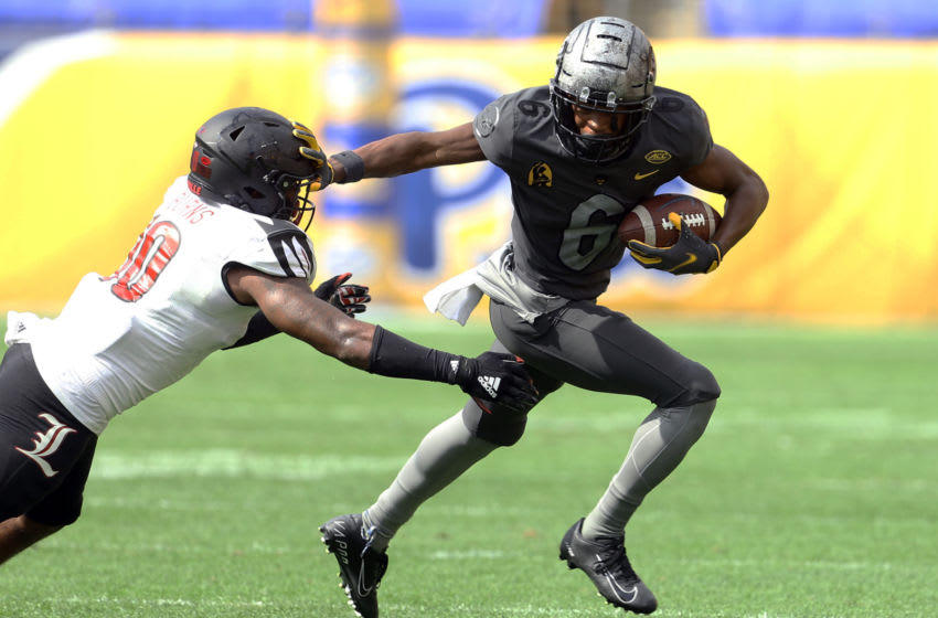Sep 26, 2020; Pittsburgh, Pennsylvania, USA; Pittsburgh Panthers wide receiver Tre Tipton (6) stiff arms Louisville Cardinals linebacker Rodjay Burns (10) after a pass reception during the fourth quarter at Heinz Field. Pittsburgh won 23-20. Mandatory Credit: Charles LeClaire-USA TODAY Sports