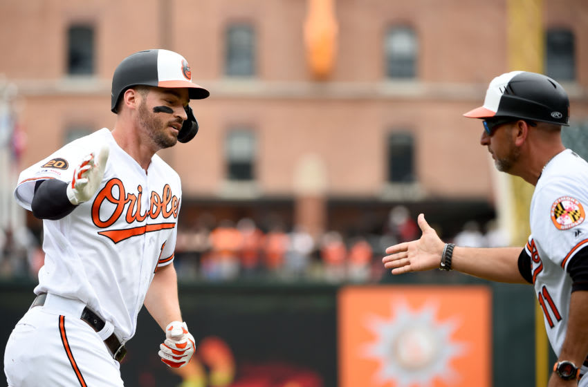 BALTIMORE, MD - JUNE 02: Trey Mancini #16 of the Baltimore Orioles celebrates with third base coach Jose David Flores #11 after hitting a home run during the first inning against the San Francisco Giants at Oriole Park at Camden Yards on June 2, 2019 in Baltimore, Maryland. (Photo by Will Newton/Getty Images)