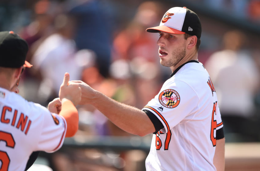 BALTIMORE, MD - SEPTEMBER 22: John Means #67 of the Baltimore Orioles in congratulated for his performance in the seventh inning during a baseball game against the Seattle Mariners at Oriole Park at Camden Yards on September 22, 2019 in Baltimore, Maryland. (Photo by Mitchell Layton/Getty Images)