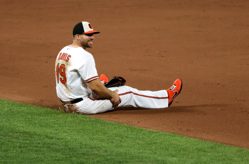 BALTIMORE, MARYLAND - AUGUST 06: First baseman Chris Davis #19 of the Baltimore Orioles sits on the ground after fielding a ball against the Miami Marlins at Oriole Park at Camden Yards on August 06, 2020 in Baltimore, Maryland. (Photo by Rob Carr/Getty Images)