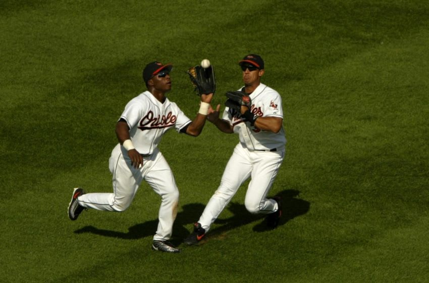 BALTIMORE - SEPTEMBER 10: Centerfielder Tim Raines Jr. #38 of the Baltimore Orioles steps in front of teammate Larry Bigbie #3 to catch a fly ball hit by Johnny Damon of the Boston Red Sox to end the fourth inning as the Red Sox defeated the Orioles September 10, 2003 at Oriole Park at Camden Yards in Baltimore, Maryland. (Photo by Doug Pensinger/Getty Images)