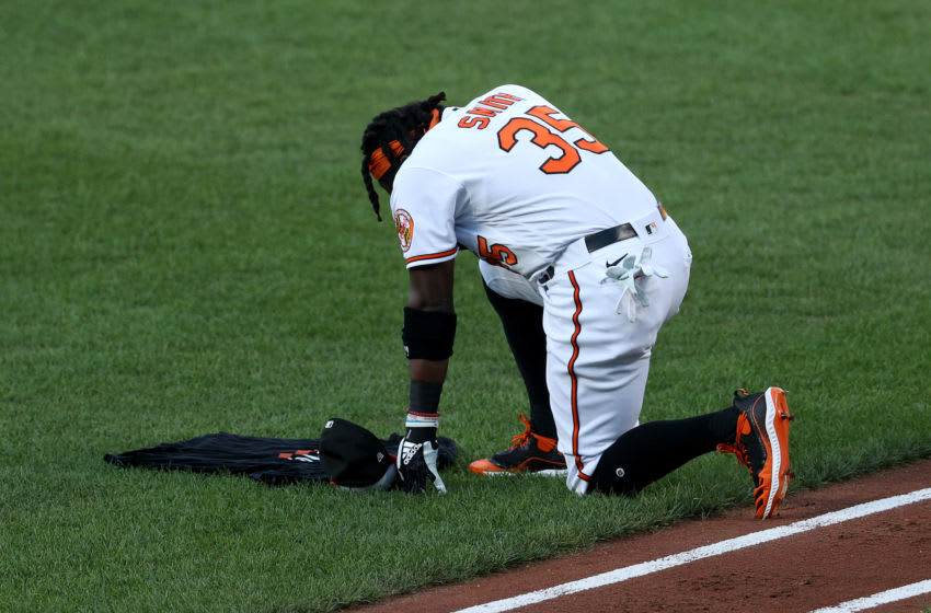 BALTIMORE, MARYLAND - JULY 29: Dwight Smith Jr. #35 of the Baltimore Orioles kneels on the field after the Orioles held a moment of silence for fan Mossila