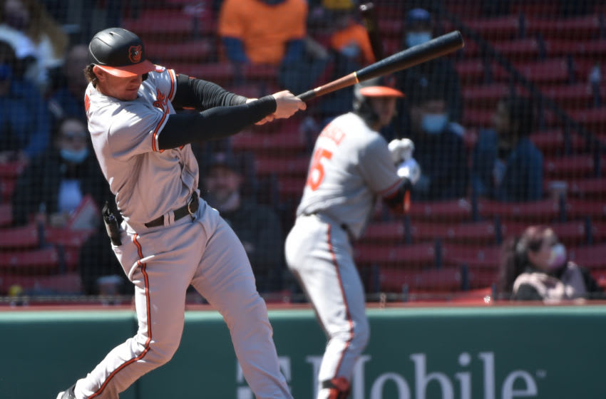 Apr 4, 2021; Boston, Massachusetts, USA; Baltimore Orioles left fielder Austin Hays (21) hits an RBI double during the third inning against the Boston Red Sox at Fenway Park. Mandatory Credit: Bob DeChiara-USA TODAY Sports