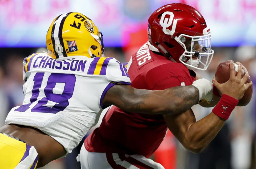 ATLANTA, GEORGIA - DECEMBER 28: Quarterback Jalen Hurts #1 of the Oklahoma Sooners is tackled by the linebacker K'Lavon Chaisson #18 of the LSU Tigers during the Chick-fil-A Peach Bowl at Mercedes-Benz Stadium on December 28, 2019 in Atlanta, Georgia. (Photo by Kevin C. Cox/Getty Images)