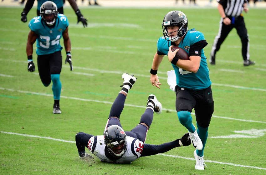 JACKSONVILLE, FLORIDA - NOVEMBER 08: Jake Luton #6 of the Jacksonville Jaguars avoids a tackle by Jonathan Greenard #52 of the Houston Texans during the second half at TIAA Bank Field on November 08, 2020 in Jacksonville, Florida. (Photo by Douglas P. DeFelice/Getty Images)