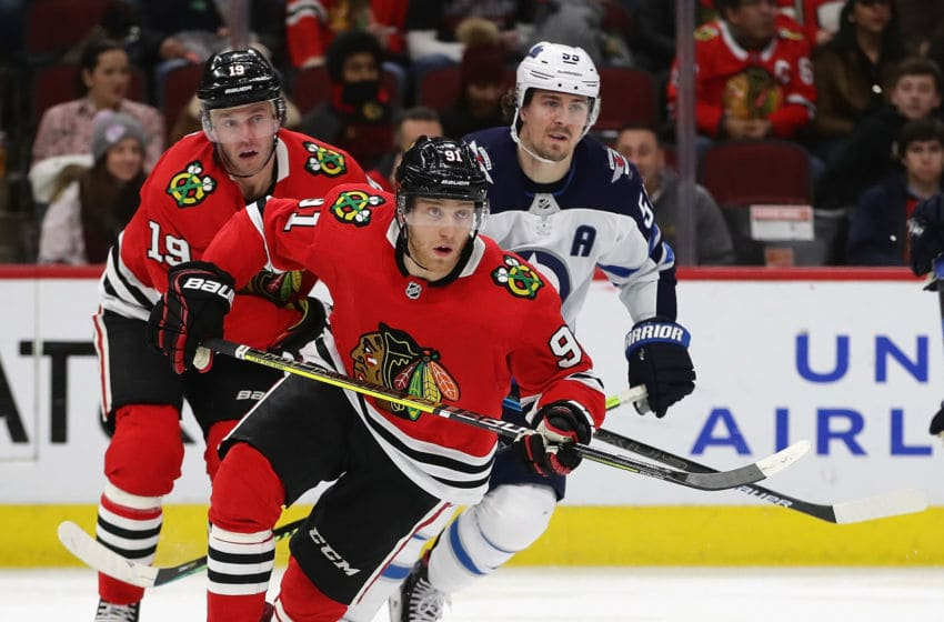 CHICAGO, ILLINOIS - JANUARY 19: Drake Caggiula #91 of the Chicago Blackhawks skates to the puck in front of Jonathan Toews #19 and Mark Scheifele #55 of the Winnipeg Jets at the United Center on January 19, 2020 in Chicago, Illinois. The Blackhawks defeated the Jets 5-2. (Photo by Jonathan Daniel/Getty Images)
