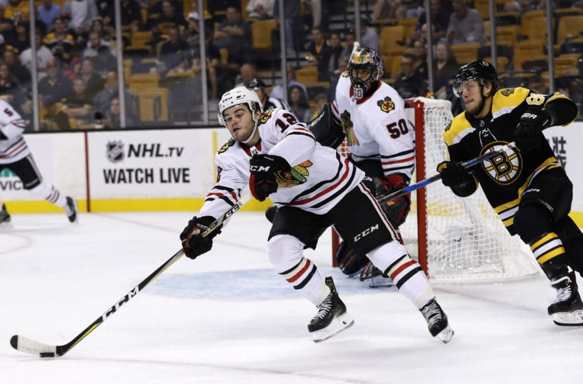 BOSTON, MA - SEPTEMBER 25: Chicago Blackhawks right wing Alex DeBrincat (12) moves the puck as Boston Bruins right wing David Pastrnak (88) closes in during a preseason game between the Boston Bruins and the Chicago Blackhawks on September 25, 2017, at TD Garden in Boston, Massachusetts. (Photo by Fred Kfoury III/Icon Sportswire via Getty Images)
